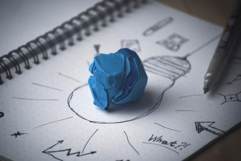 finanzielle-freiheit-Skizze-Glühbirne-Blauer-Papier-Knaeuel