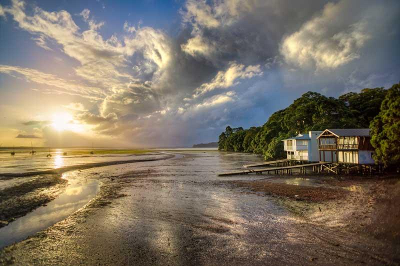 Strand-mit-Strandhaus-bei-Sonnenuntergang