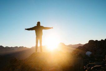 Mann-steht-auf-Berg-bei-Sonnenaufgang