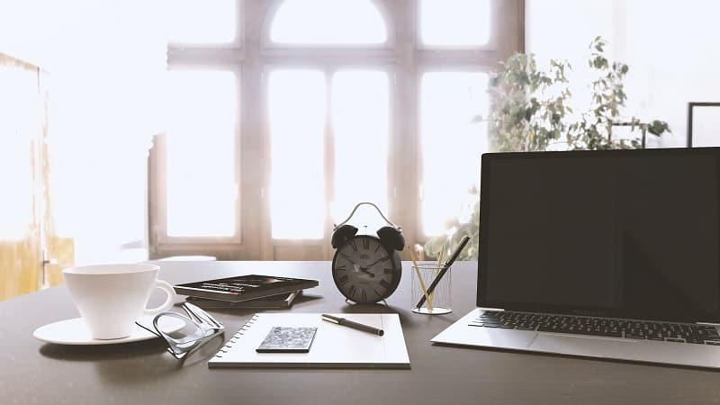 Schreibtisch-mit-Laptop-Uhr-Block-Kaffetasse
